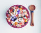 Aerial view of a raw buckwheat and blueberry bowl with a wooden spoon next to it