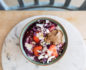 Aerial shot of a marble chopping board with a bowl of rolled oats with blueberry-maple compote