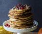 White cake stand with a tall stack of pancakes with chocolate syrup on top