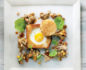 Aerial shot of a square white plate with egg in the hole with wild mushrooms