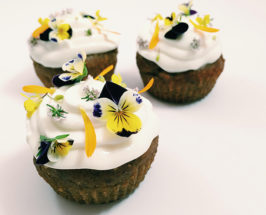 Close-up of 3 gluten-free cupcakes with white topping and flowers