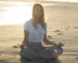 Woman on the beach in a meditation pose with selenite crystals in both hands