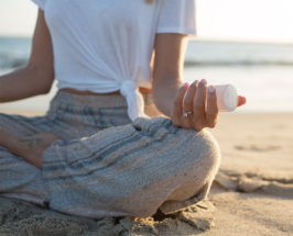 Close-up of a woman in meditation position on the beach holding a selenite crystal in her hand