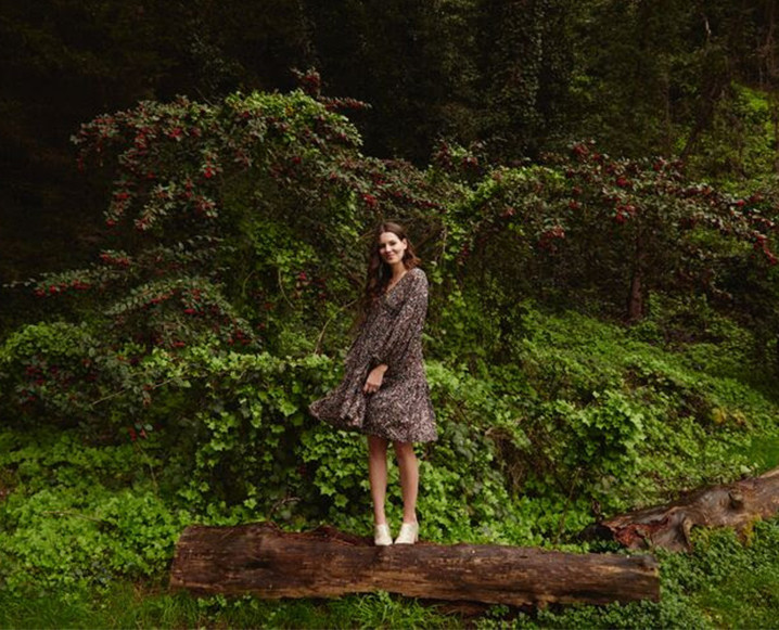 Katie Hintz, Mother Mag founder, standing on a log in the forest