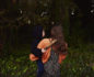 Back of Katie Hintz, holding her son, walking into the forest