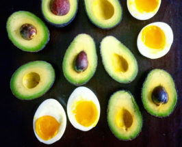 Aerial shot of multiple pieces of mini avocado and hard-boiled eggs, all cut in half