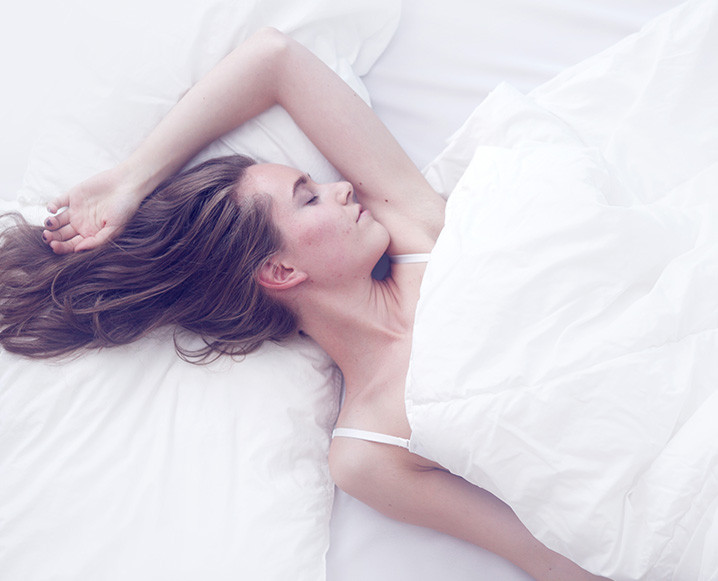 Medium shot of a woman sleeping in bed between white sheets