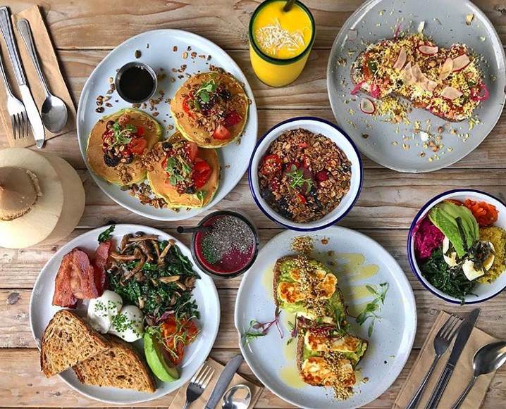 Aerial view of a table with brunch dishes, including pancakes, toast, poached eggs and more