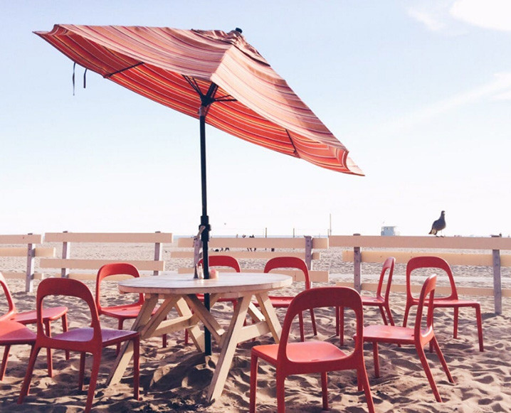 Photo of Back on the Beach Cafe with a round table and red chairs under a red umbrella on the beach