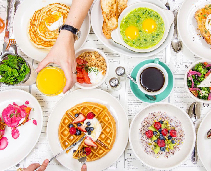 Aerial view of a brunch spread at Jack's Wife Freda restaurant showing eggs, waffles, pancakes and more