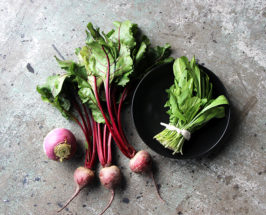 Aerial view of a bunch of radishes and a round tray with arugula salad