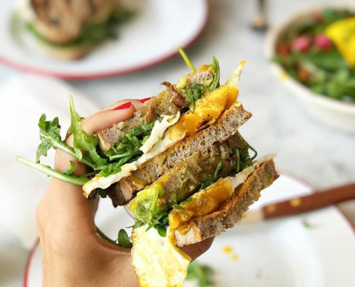 Close-up of a woman's hand holding a tall sandwich made with organic gluten-free bread