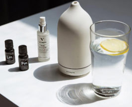 Tabletop with 2 small frankincense bottles, a spray bottle, large Vitruvi bottle and a glass of water with a slice of lemon