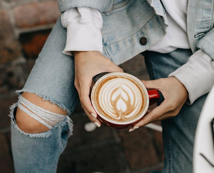Two hands holding a red coffee mug with a latte with a flower-shaped foam