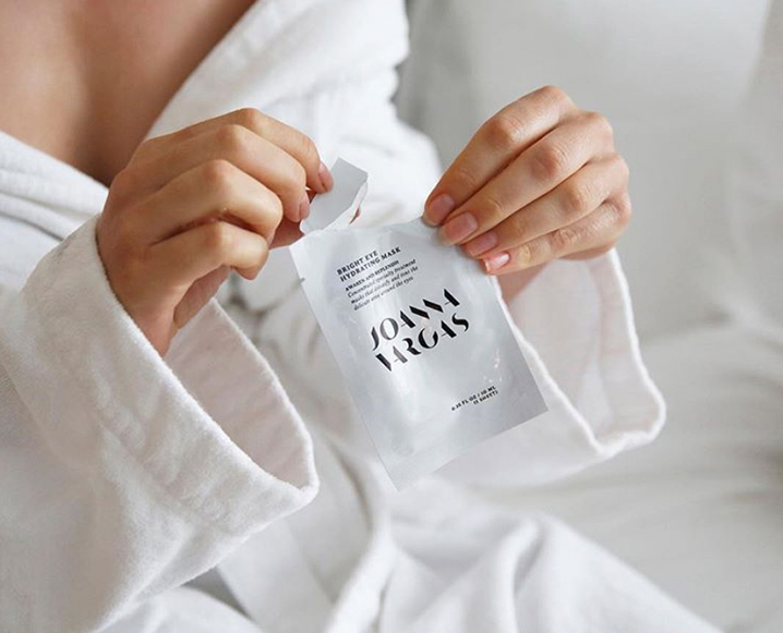 Close-up of a woman in a white bathrobe opening a sample sachet of Joanna Vargas Bright Eye Hydrating Mask