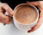 Close-up aerial view of 2 hands holding a ceramic mug with almond hemp milk