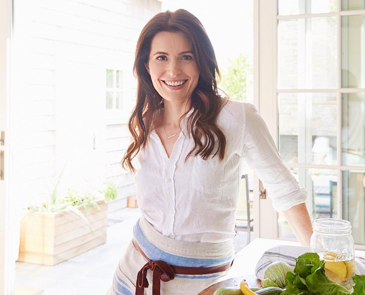 Woman wearing a white shirt and a cooking apron standing in a kitchen decor