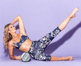 Lauren Roxburgh in a rolling foam pose on a purple background