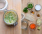 Split photo with a mason jar soup on the left and soup ingredients in glass bowls on a wooden table on the right