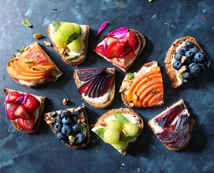 Aerial shot of a stone board with half-cut slices of toast with various fruit toppings