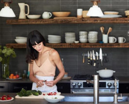 Woman chopping vegetables on a chopping board in a kitchen background