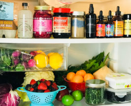 Close-up of the inside of a fridge with wellness jars on the top shelf and fruits & vegetables on the bottom