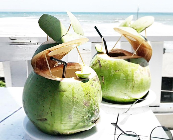 Patio table with 2 green coconut drink containers with black straws and view of the ocean in the background