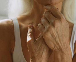 A neck-down image of a senior woman with wrinkled skin clasping her hands