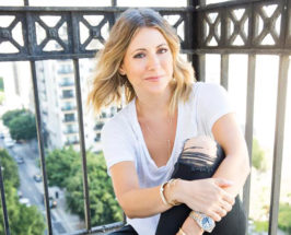 fine jewelry Designer Zoe Chicco in white shirt and ripped jeans smiling at camera