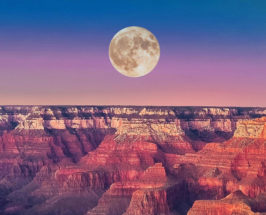 Long shot of a canyon with a full moon on a blue and purple sky