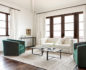 Long shot of a living room with white sofa, 2 green armchairs and art deco coffee tables