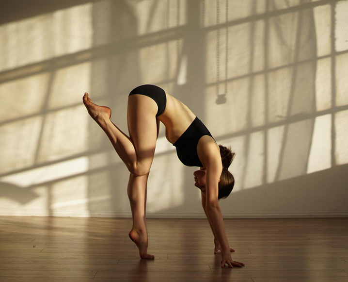 Woman performing a stretching routine in a studio background