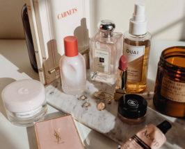 Countertop with multiple items, Jo Malone perfume bottle, YSL perfume, Chanel makeup, Quai bottle, lipstick & jewelry