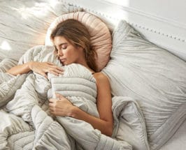 girl sleeping in blankets recovering mitochondrial health