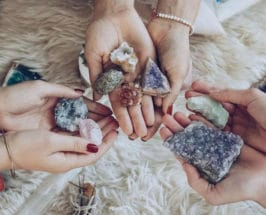 Three pairs of women's hands holding different types of crystal with various shapes and colors