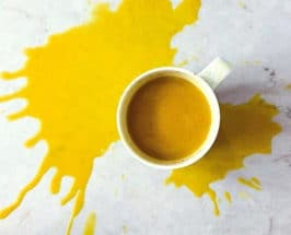 How To Use Turmeric latte splashed on grey counter top overhead
