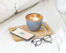 breethe app open on a phone with coffee in bed